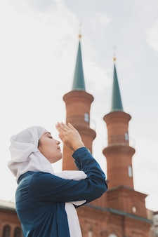 Muslim woman prayer wear hijab fasting pray to allah on mosque