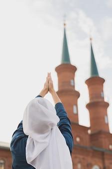 イスラム教徒の女性の祈りは、モスクの背面図でアッラーにヒジャーブの断食の祈りを着用します