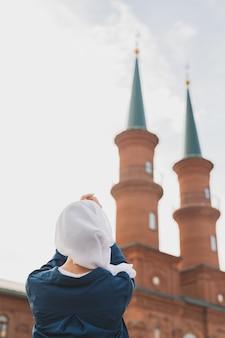 이슬람 여성의 기도는 이슬람 사원 배경에서 알라에게 히잡 금식 기도를 하고 있다