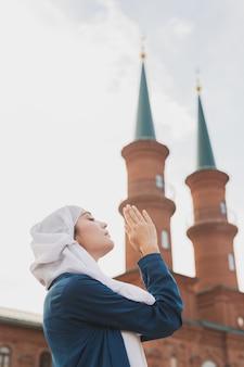 イスラム教徒の女性の祈りは、モスクでアッラーにヒジャーブの断食の祈りを身に着けています