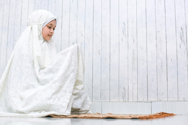 Мусульманка молится богу с молящим жестом руки на молитвенном коврике