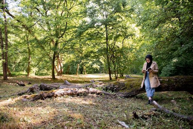 彼女の自由な時間の間に公園で本を読んでいるイスラム教徒の女性