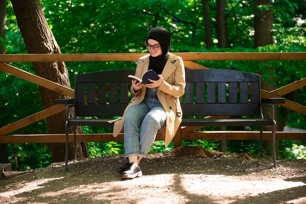 Muslim woman reading a book in the park during her free time