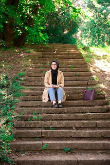 Muslim woman reading a book in the park during hers free time.