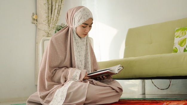 Muslim woman reading the quran seriously at home