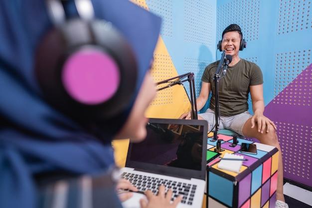 스튜디오에서 남자와 팟캐스트를 녹음하는 이슬람 여성