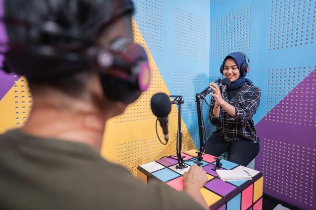 スタジオで男性とポッドキャストを録音するイスラム教徒の女性