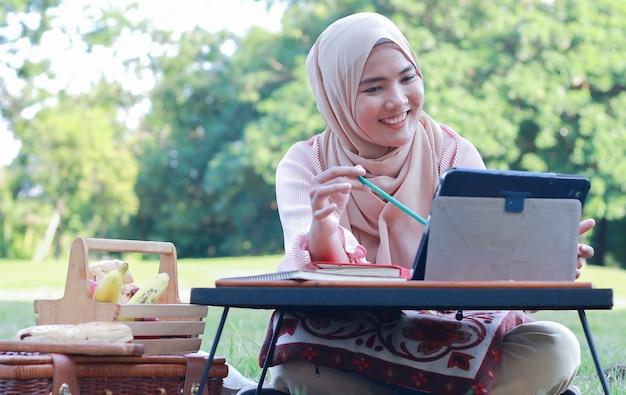Мусульманская женщина отдыхает и работает в парке на отдыхе
