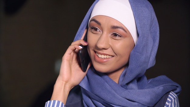 Muslim woman smiling talking on a cell phone.
