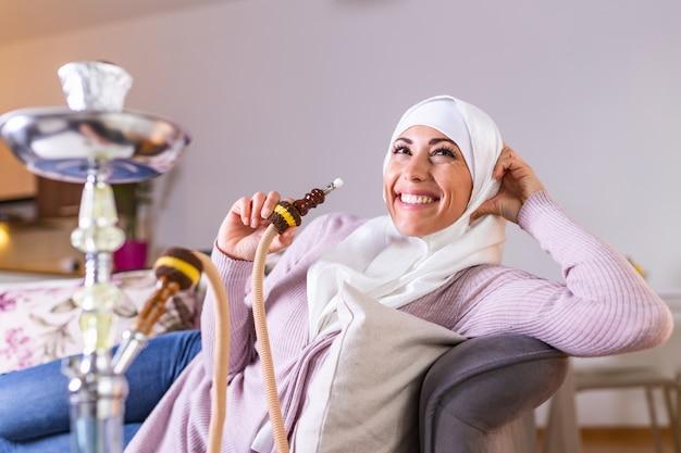 Мусульманская женщина курить кальян дома. арабская девушка курит кальян