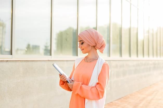 문서 용지를 들고 서 있는 이슬람 여성