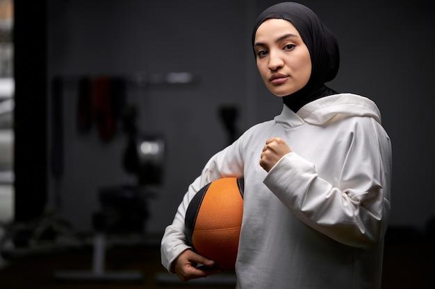 イスラム教徒の女性はトレーニング後にカメラにポーズをとってバスケットボールのボールで立っています、若い女性はヒジャーブを着てスポーツに従事しています