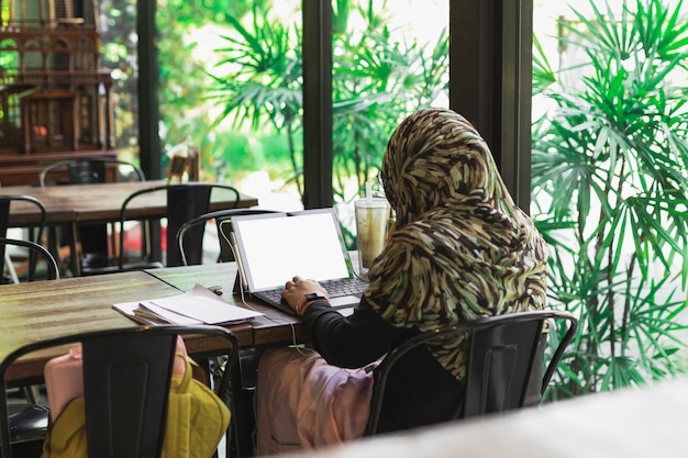 Muslim woman student in hijab working on laptop at coffee table.