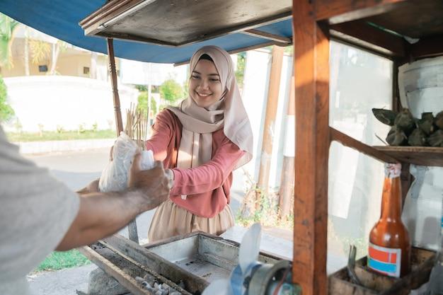チキンサテから食べ物の注文を受けているイスラム教徒の女性