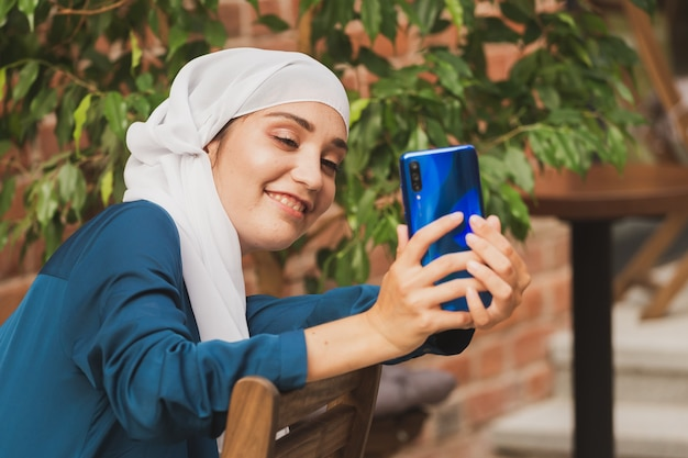Muslim woman taking selfie happy beautiful girl with scarf take picture of her self using smartphone