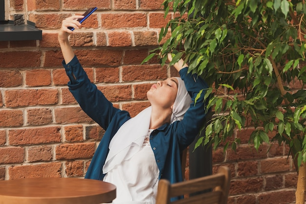 Muslim woman taking selfie. happy beautiful girl with scarf take picture of her self using smartphone.