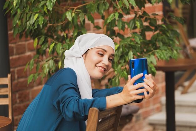 自撮りをしているイスラム教徒の女性。スカーフと幸せな美しい女の子は、スマートフォンを使用して自分の写真を撮ります。