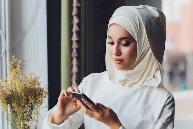 카페에서 휴대 전화 통화하는 이슬람 여성