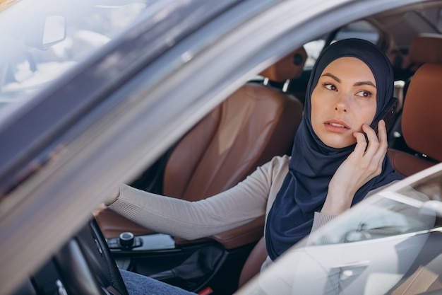 Muslim woman talking on the phone in her car