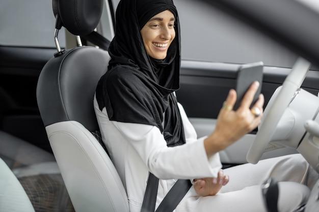 차를 운전하면서 전화통화를 하는 이슬람 여성