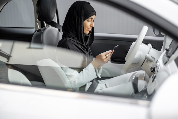 Muslim woman talks on phone while driving a car