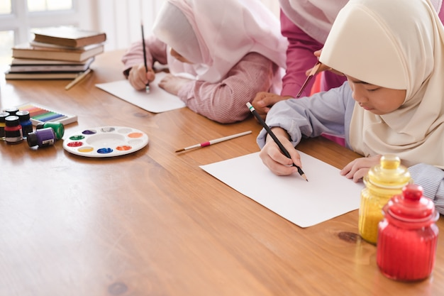 Muslim woman teaching her children painting and drawing at home.