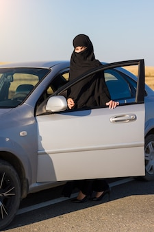 Мусульманка путешествует на машине. традиционная одежда Premium Фотографии