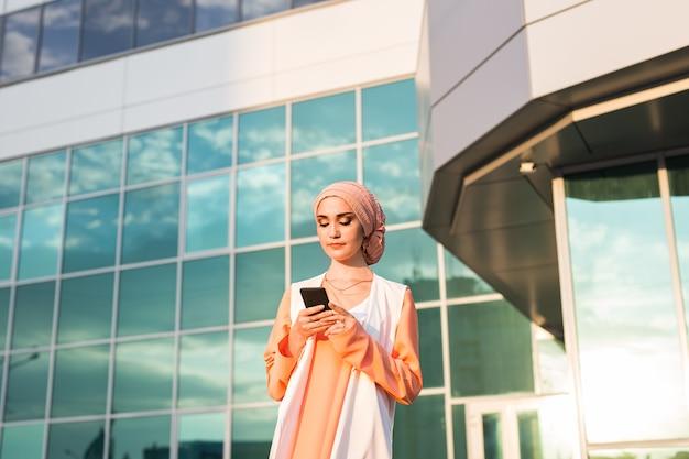 電話を使用してイスラム教徒の女性。スマートフォンを保持しているヒジャーブの実業家