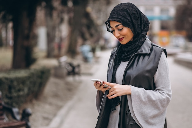 Muslim woman using phone outside in the street
