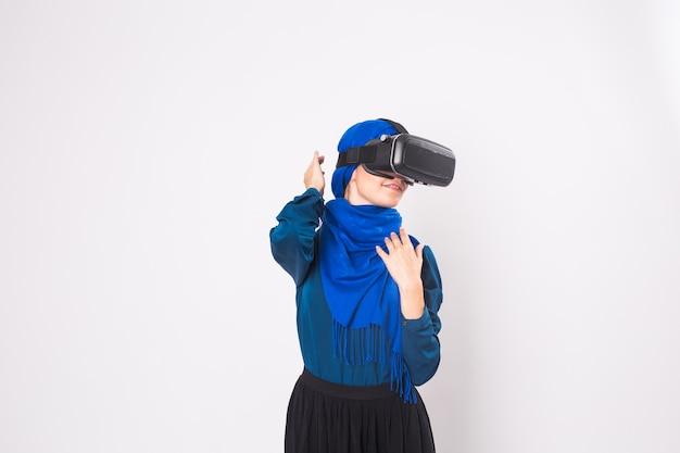 Мусульманская женщина с помощью гарнитуры vr. технологии, vr, люди и концепция игры.
