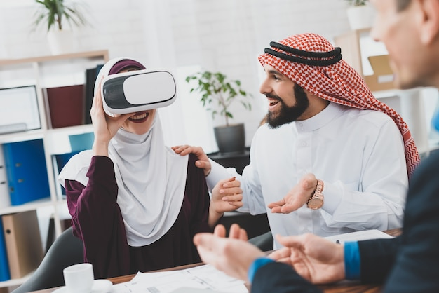 Muslim woman in vr headset watching new house.