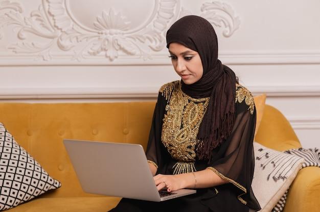 働くヒジャーブを身に着けているイスラム教徒の女性