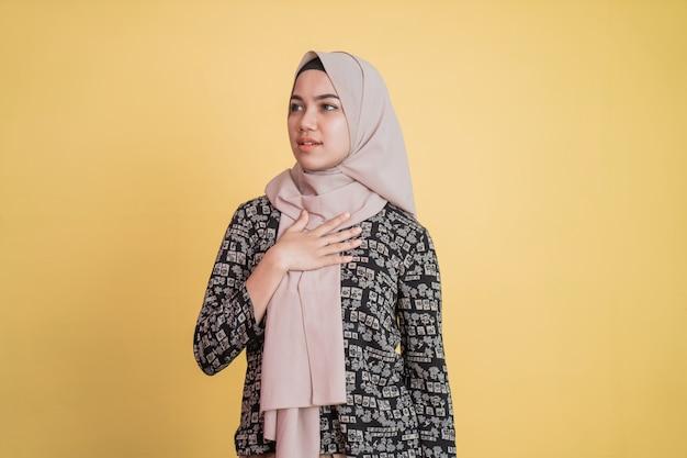차분한 표정으로 가슴을 잡고 히잡을 쓴 이슬람 여성