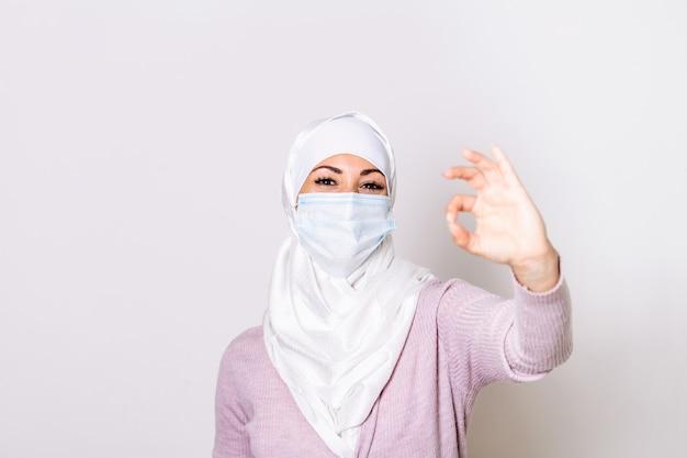 Мусульманская женщина, носить медицинский маска, портрет в студии. женщина в хиджабе в защитной маске и показывает знак ок