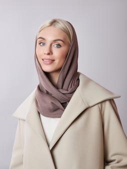 Мусульманская женщина со светлыми волосами в платке платка оделась на голове.