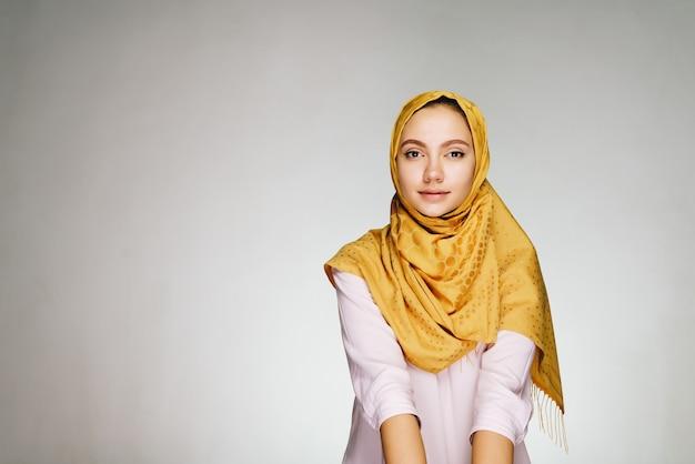 밝은 스튜디오에서 노란색 목도리에 진정 얼굴을 가진 무슬림 여성