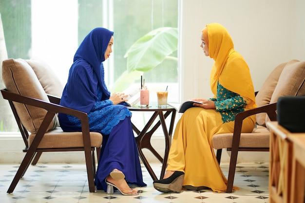 カフェで本を持つイスラム教徒の女性