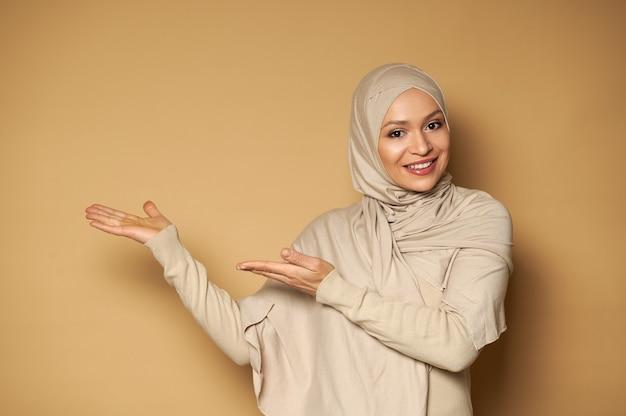 ヒジャーブで覆われた頭を持つイスラム教徒の女性はベージュの表面の側面を指し、正面を見ながら歯を見せる笑顔で微笑む