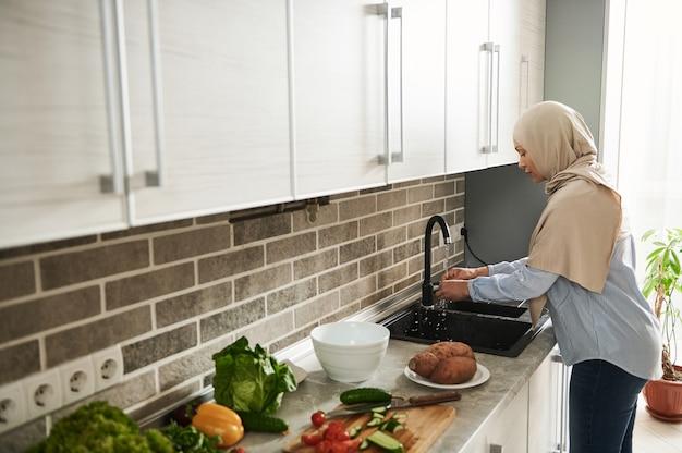 부엌에서 야채 잎을 세척하는 덮여 머리와 무슬림 여성.