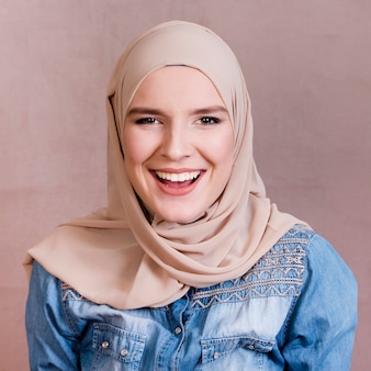 Muslim woman with headscarf laughing in front of colored backdrop