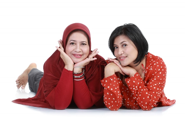 Muslim woman with her daughter lying on isolated over white backround