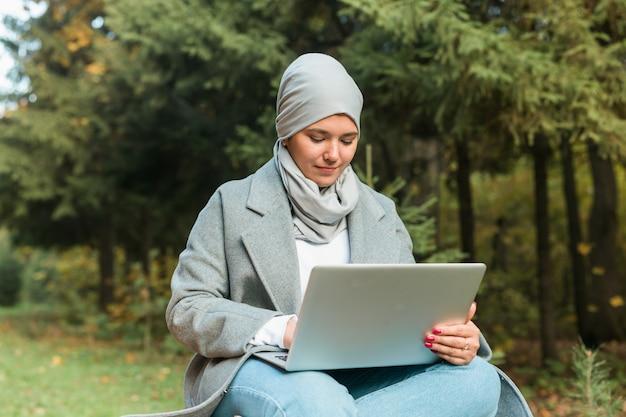공원에서 노트북을 들고 있는 이슬람 여성
