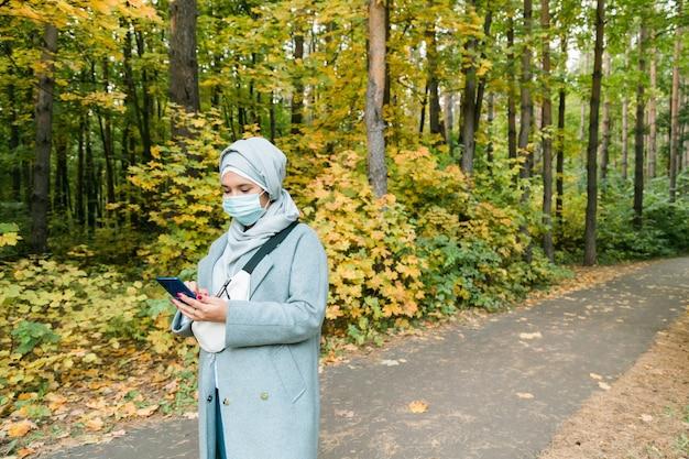 히잡을 쓴 이슬람 여성이 야외에서 얼굴 마스크를 쓰고 있다. 코로나바이러스, 건강 관리 및 전염병 개념. 복사 공간