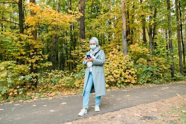 히잡을 쓴 이슬람 여성이 야외에서 얼굴 마스크를 쓰고 있다. 코로나바이러스, 건강 관리 및 전염병 개념. 광고를 위한 공간