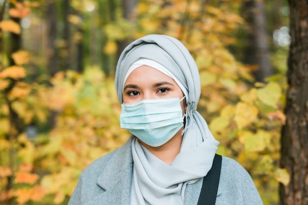 히잡을 쓴 이슬람 여성이 야외에서 얼굴 마스크를 쓰고 있다. 코로나바이러스, 건강 관리 및 전염병 개념.