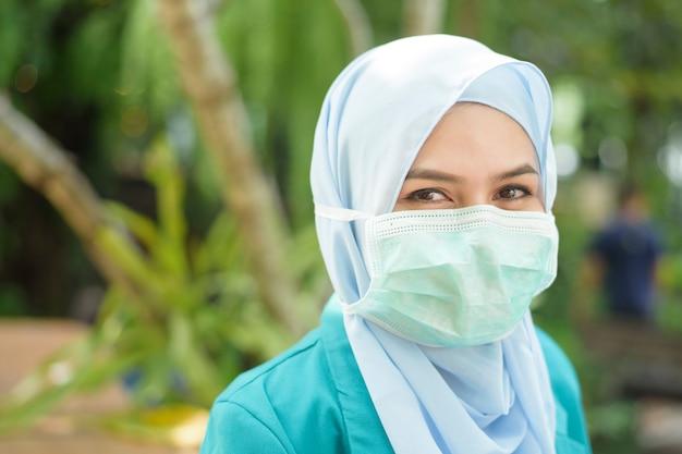 Мусульманская женщина с хиджабом носит маску на открытом воздухе