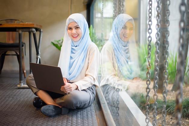 Мусульманка с хиджабом работает с ноутбуком в кафе