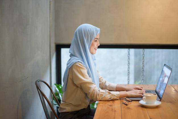 ヒジャーブとイスラム教徒の女性はコーヒーショップでラップトップコンピューターで働いています。