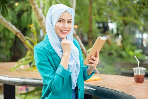 Muslim woman with hijab is working with tablet in coffee shop