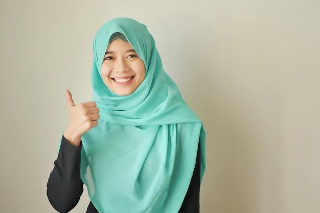 엄지손가락을 가리키는 히잡을 쓴 이슬람 여성